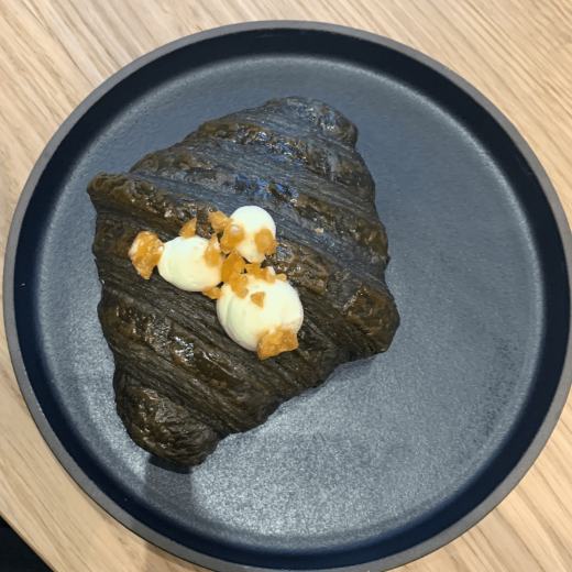 Black caramelised banana croissant with 3 blobs of cream on it sitting on a round metallic plate on a wooden table.