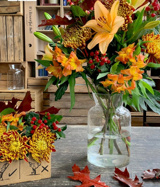 Image of a mix of fall leaves coloured flowers in a clear vase. There's a smaller bunch in a box to the right of the vase and a few leaves on the table. There are kitchen cabinets in the background.